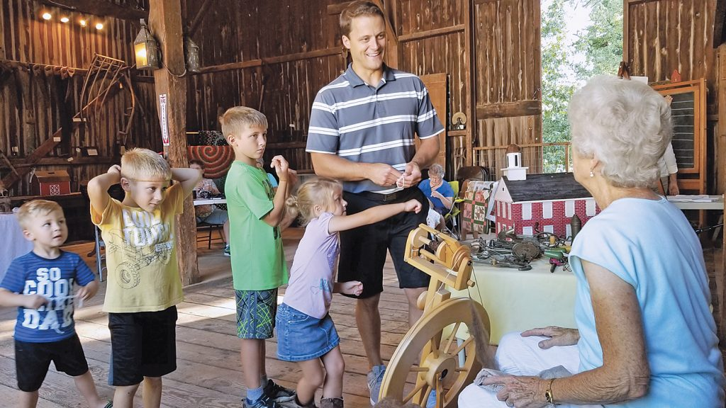 Kevin G. Johnson, Sweden Town Supervisor, and his children Reagan, Grant, Kevie and Maggie, enjoyed learning from Marion Dilger how cotton was spun into yarn.
