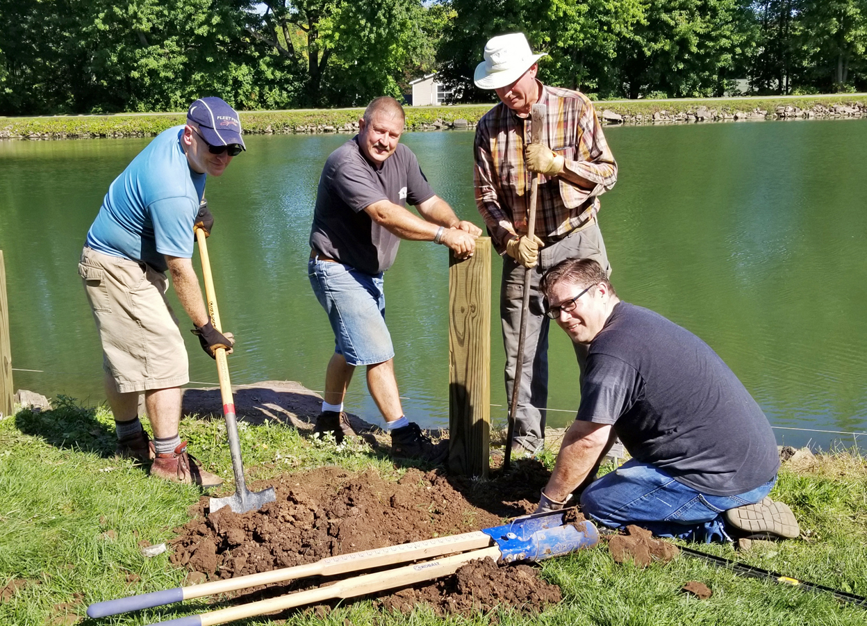 "Four men installing posts at canal (left to right) Jeff Snarr, Harry Donahue, Paul DeGraff and James McKinney are part of a volunteer team at the canal installing six posts which will be part of the boat dock. All are members of the Church of Jesus Christ of Latter-Day Saints in Brockport, except Harry Donohue, superintendent of the DPW. The project could be completed in the spring or fall when post footers can be installed in the drained canal. The final project will be a floating dock 60 feet by eight feet reached by a 44-foot ramp and a ""gangway."" Photo by Dianne Hickerson"