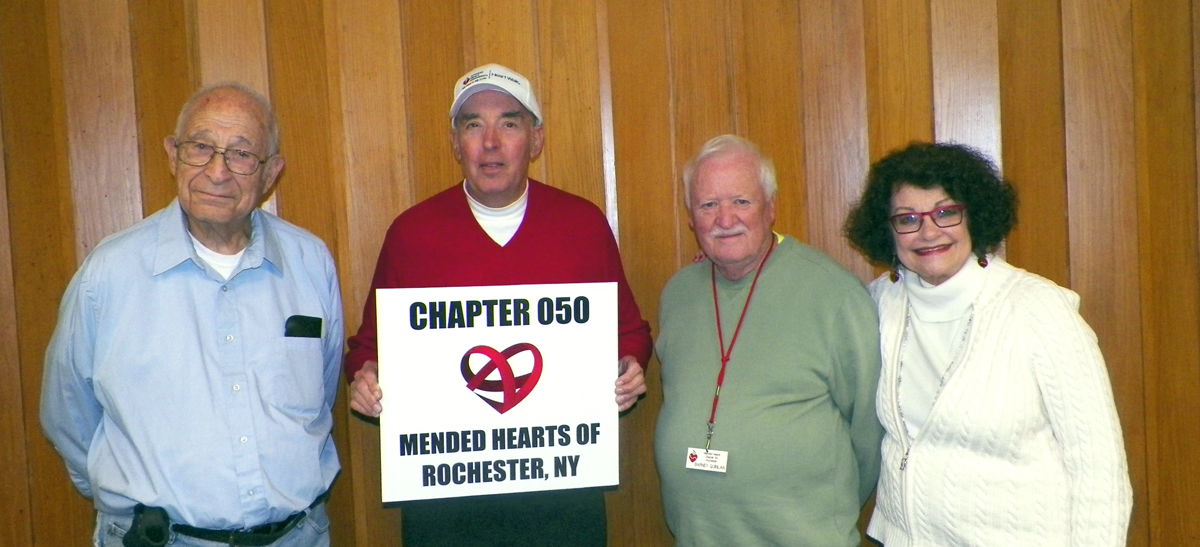 Bruce Rychwalski (holding sign) with Mended Hearts President Bernard Quinlan, Vice-President Eugene Binder and Program Chairman Marlene Adams.