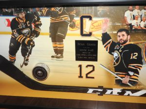 Shadowbox created with mementos from Brian Gionta's 1,000th NHL Game including his hockey puck and stick and several photos from the game held on March 27, 2017. Photo by Karen Fien