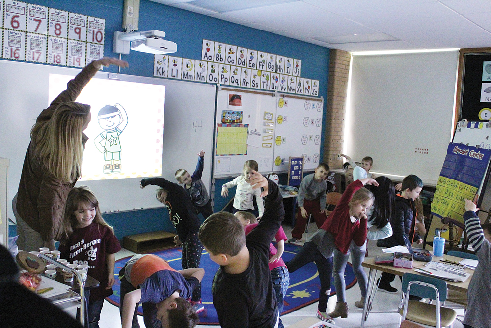 Ayn Gardner's kindergarten class stretches during Fitness & Fluency, an exercise where they identify shapes and numbers displayed on the interactive board then pause for a physical activity.