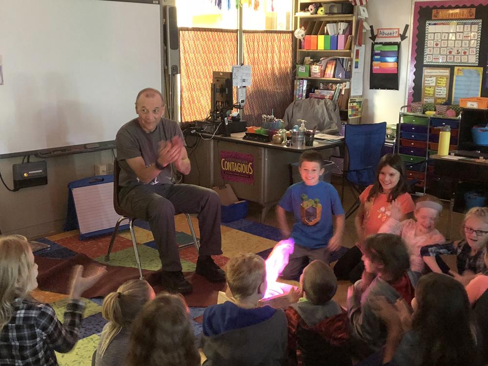 "Rick Merritt shares stories and activities around an indoor ""campfire."""