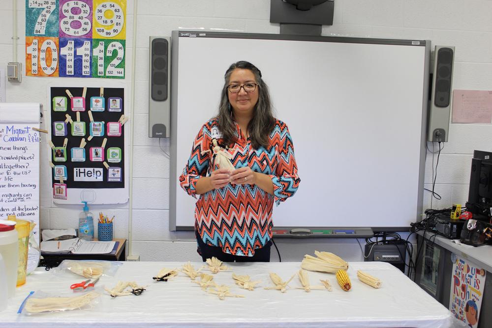 Michelle Caballero teaches students how to make corn husk dolls.