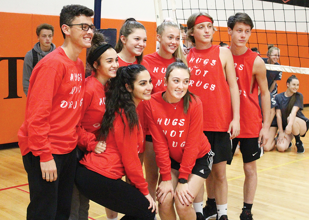 Student members of the volleyball team Hugs Not Drugs show off their unique, Red Ribbon-themed uniforms. Provided photo