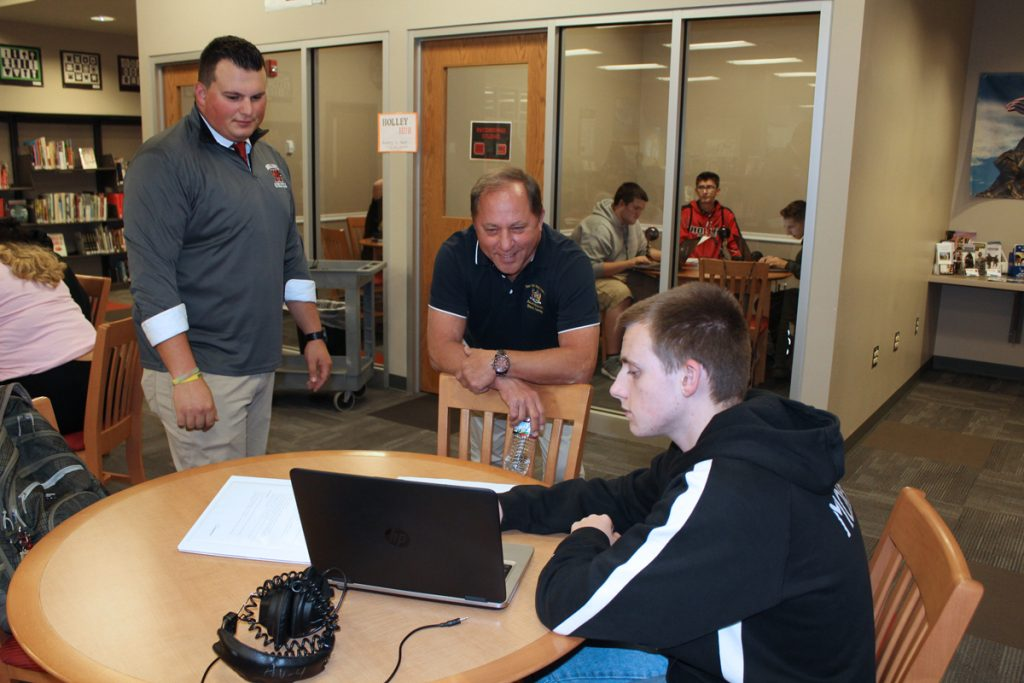 From left, Current Events teacher Nick D'Amuro and Assemblyman Hawley listen to student Greg Morrill explain editing the podcast.