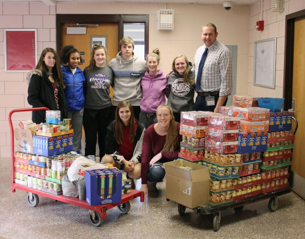 Byron-Bergen Varsity Club members with a few of the hundreds of donated items collected for the Holiday Food Drive.
