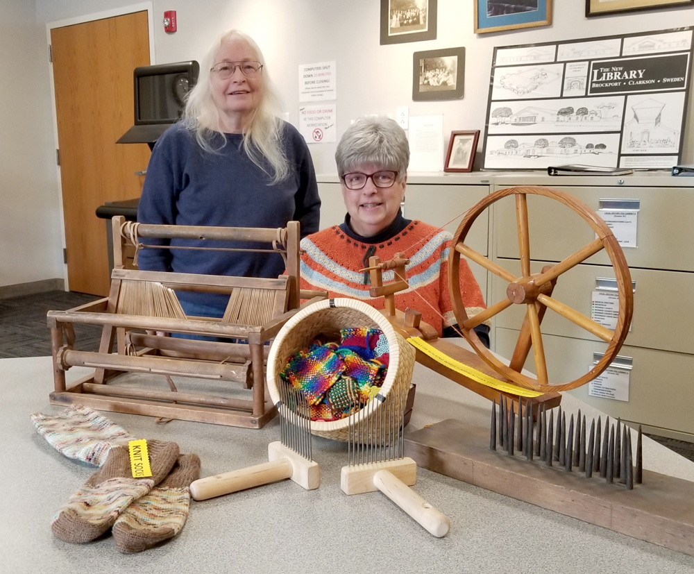 "In the Local History Room Kathryn Tsoukatos (left) and Cathy Chesnut arranged the display showing ""Fiber preparation through the ages."" They placed some of the pieces on a table for the photo. In the background are, left to right: A small ""Peacock"" 12-inch loom; a basket of woven samples from miniature looms; a salesman's sample of an Appalachian style ""walking"" spinning wheel. In the foreground left to right are: Knitted wool socks; a pair of fiber combs used on shorter plant or animal fibers to prepare them for  spinning; and, a ""hackel"" used to line up long fiber for spinning. Photo by Dianne Hickerson"