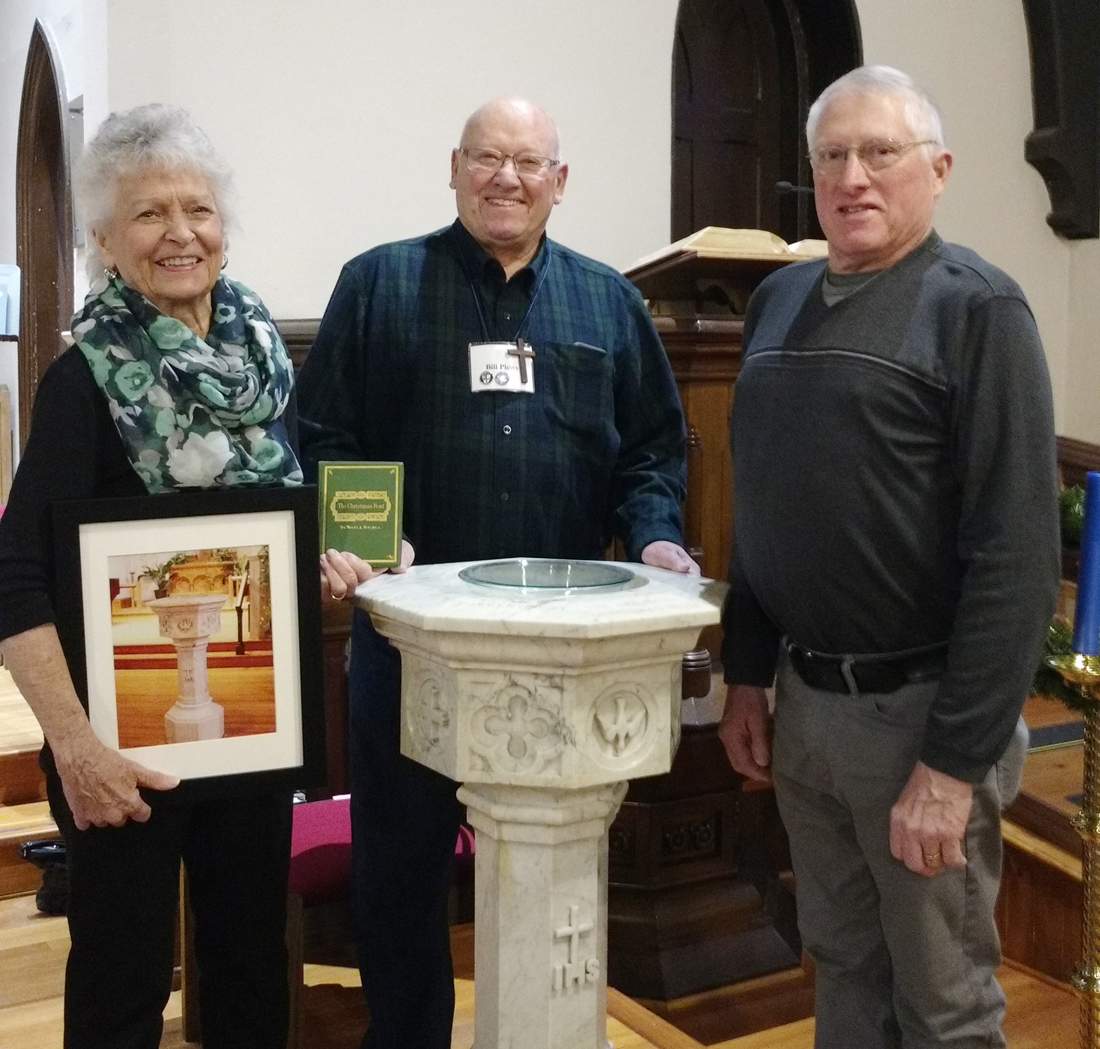 "Bill Plews and Norm Knapp, son of the late Emily L. Knapp, present a copy of the book ""The Christmas Font,"" penned by Brockport resident Mary Jane Holmes, to Susan Savard, head of volunteers at the Emily Knapp Museum. The book is a gift from St. Luke's Episcopal Church to the Emily Knapp Museum."