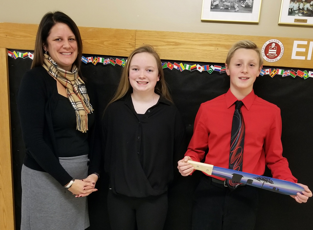 Tracie Czebatol, Merton Williams Middle School principal, and eighth graders Sarah Williams and Jacob Runyan presented information about the Ugandan Water Project at the December 11 Hilton Board of Education meeting. Jacob is holding a hand-painted machete sent to him after he raised $190 for a rainwater collection system.