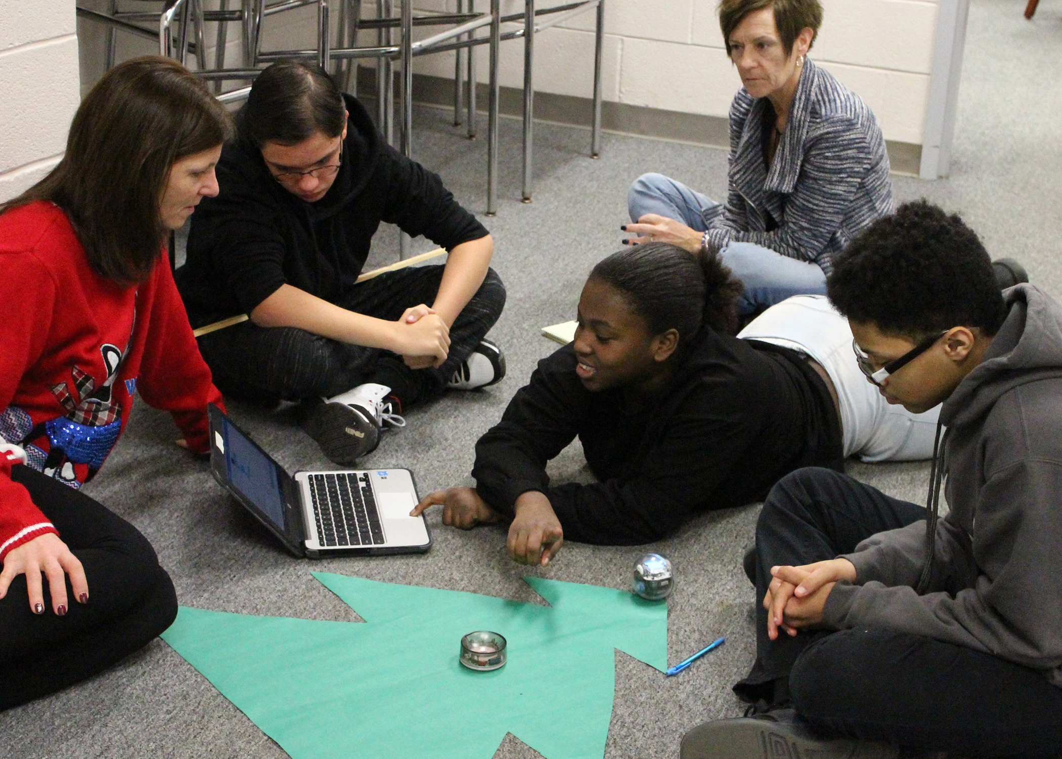 Teacher Nancy McMahon (left) works with students who are designing a coding program that will enable their Sphero Bolt robot to travel along the perimeter of the green tree shape.