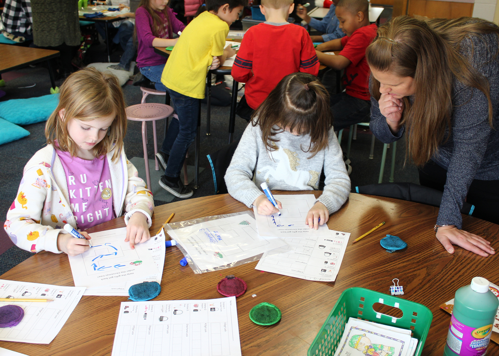Chestnut Ridge School first-grade teacher Jodi Piontkowski (right) works with students at Station 3 as they navigate a maze. Each team solves six different puzzles during the course of the class.
