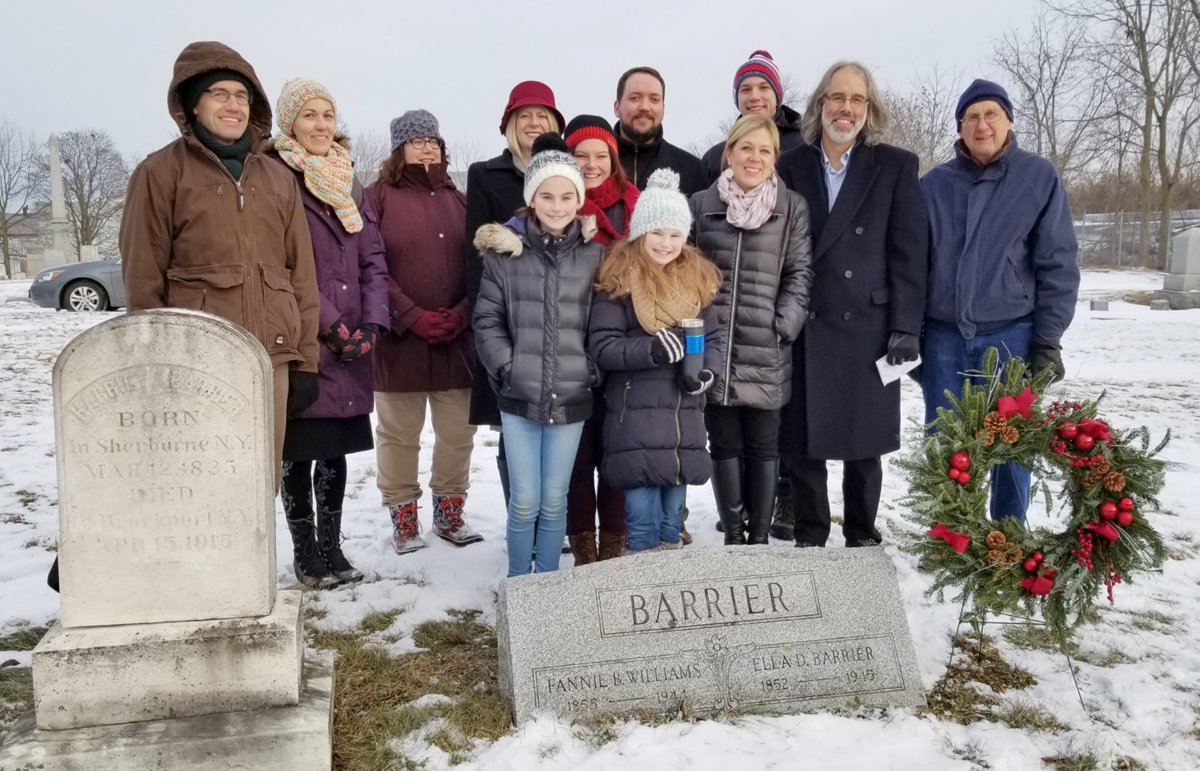 """This photo was taken in the High Street Cemetery at the gravestone marking both graves of the Barrier sisters: Ella D. Barrier 1852-1945; Fannie B. Williams 1855-1944. Two gravestones to the left mark the graves of their parents. Back row (l-r): Robert LeSuer, PhD, Chemistry Dept, The College; Rozenn Bailleul-LeSuer, PhD., Historian, WMHS; Julie Pruss, Assistant to the President, The College; Heidi Mcpherson, PhD., President, The College; Pastor Dan Brockway, First Baptist Church of Brockport; Cory Albrecht, sophomore at the University of Massachusetts at Lowell; Christopher Albrecht, teacher and Program Coordinator, Brockport Hill School; Gordon """"Gordy"""" Fox, President, WMHS. Front row (l-r): Sadie Contrera, sixth grade; Katie Contrera, mom; Genni Contrera, fifth grade; Susan Hasenauer, Assistant to Superintendent for Elementary Instruction, Brockport School District. Photo by Dianne Hickerson"""