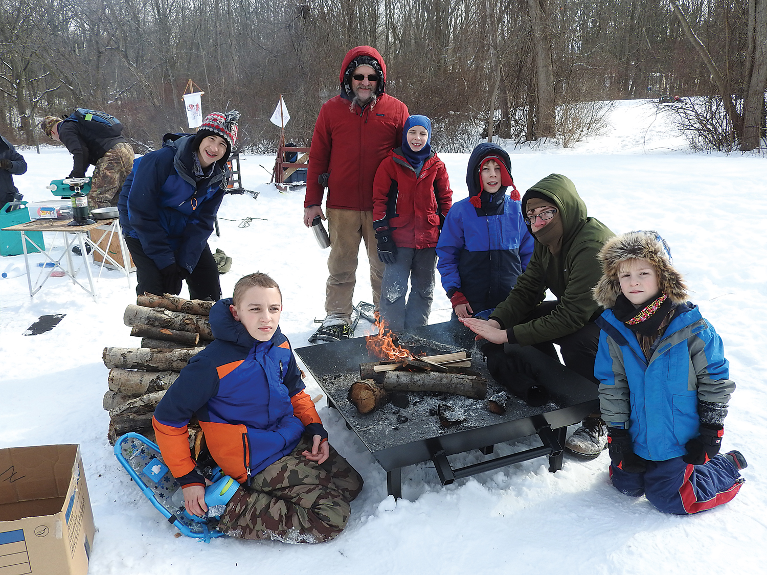 Hamlin's Troop 324 warming up by the fire at their camp site.