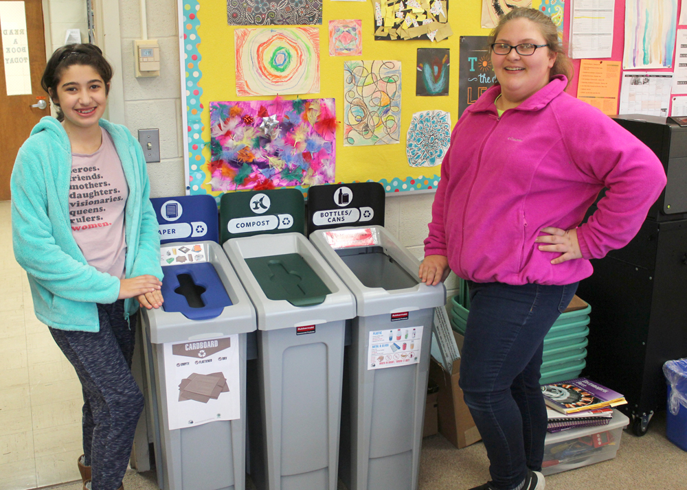 Seventh-graders Jessica Magguilli and Kathryn Parisi show off some of the new recycling bins. Other seventh-grade team members include: Adrian Borchers, Ryan Giglia, McKenzie Ennis and Isabella Mettler.