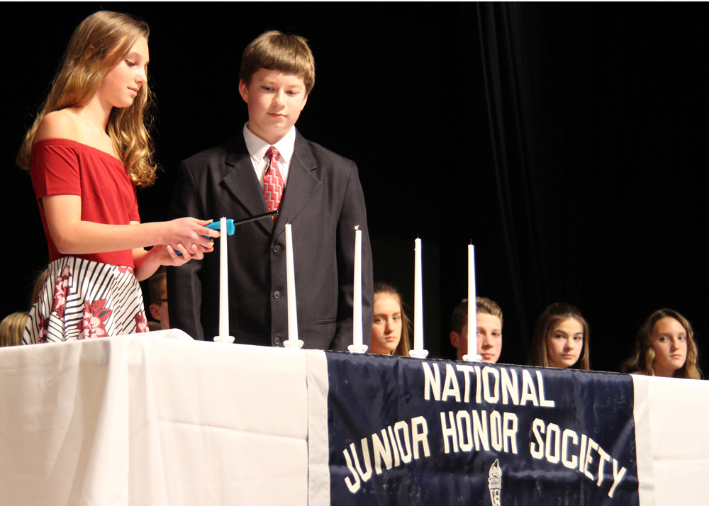 Samantha Fisher and Alexander Richmond light candles representing the five characteristics of membership during the Merton Williams Middle School National Junior Honor Society induction ceremony.