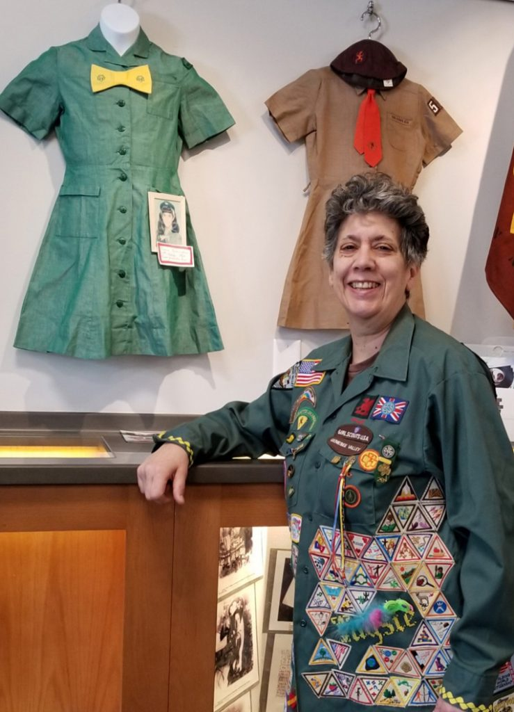 Taysie Pennington stands near two uniforms she wore as a Girl Scout. The brown one was for her Brownie Girl Scout membership in 1966. The next year she moved up to Intermediate Girl Scout (the name then) and wore the green uniform. The photo attached for display shows her wearing it in fifth grade. Her jacket she is wearing displays a wide variety of Scout badges and pins. Photo by Dianne Hickerson