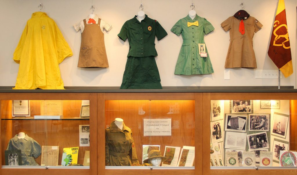 One wall in the Local History Room shows uniforms provided by Taysie Pennington. The two on the right belong to Taysie and are explained in another photo. The yellow raincoat is Taysie's, used in summer camp. The next is a Brownie uniform. The green one is a Senior Scout uniform, both obtained at VOA and their dates are unknown. The central display case contains the 1919 first Scout uniform, sash and merit badges. Photo by David Q. McDowell
