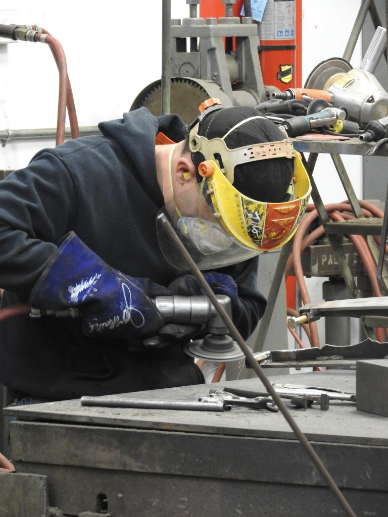 Worker in fabrication studio using a grinder.
