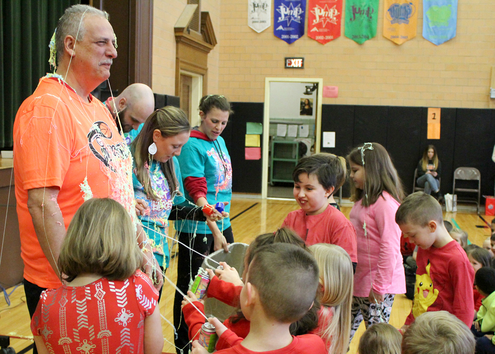 Student representatives celebrated meeting the fundraising goal by covering teachers and administrators, incuding Principal David Johnson, with sticky silly string.