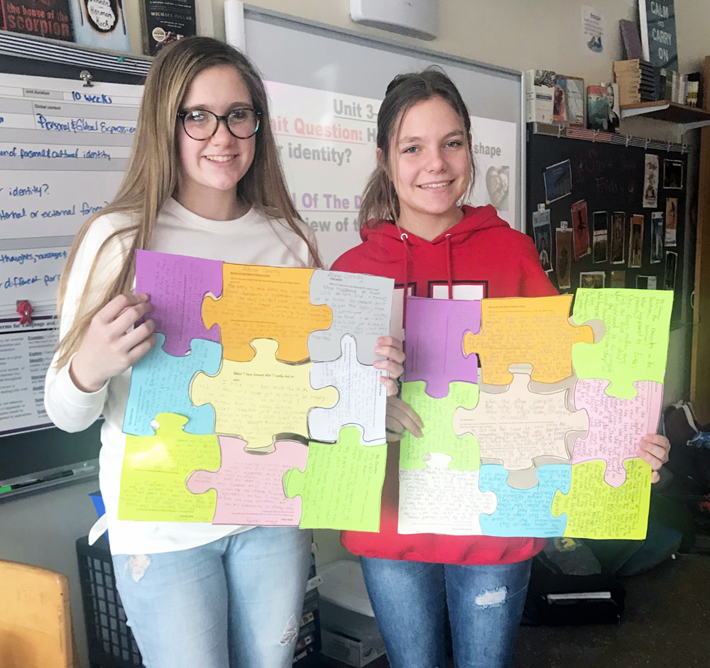 "Alana Conolly (left) and Mia Geiger, eighth graders at Merton Williams Middle School, show off their completed ""puzzles."" Each piece illustrates central themes found in the children's books they read about the Holocaust."