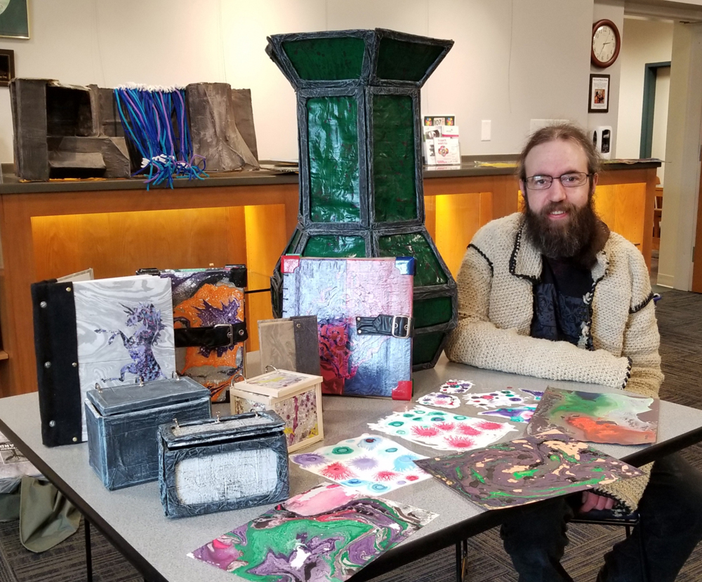 "Andrew sits with some of the objects that will appear in the display cases at Seymour Library and explains how they are crafted. He is wearing one of his pieces, a jacket made out of large-diameter hemp twine tied in knots. The large green item is a vase featuring abstract paint. The base is made of cardboard with papier mache over, painted and covered with a substance to make it shine. The sections are framed with cardboard strips, covered with papier mache and painted. In the foreground are colored paintings made with water and swirls of paint. The lighter pieces lying flat are made from white paint on plastic; over it dots of ink mixed with isopropyl alcohol branch out from the chemical reaction. With variations in each, the three boxes are made from double-layer cardboard and wrapped with abstract painting on paper.  Painted popsicle sticks make a frame around the sides. About the four books standing, Andrew said, ""I learned bookbinding at college and kind of went wild with it,"" Andrew said. ""The three larger ones are sketch books, made with blank paper. The smaller one is an old science fiction novel from bargain bin that I wrapped."" Photo by Dianne Hickerson"