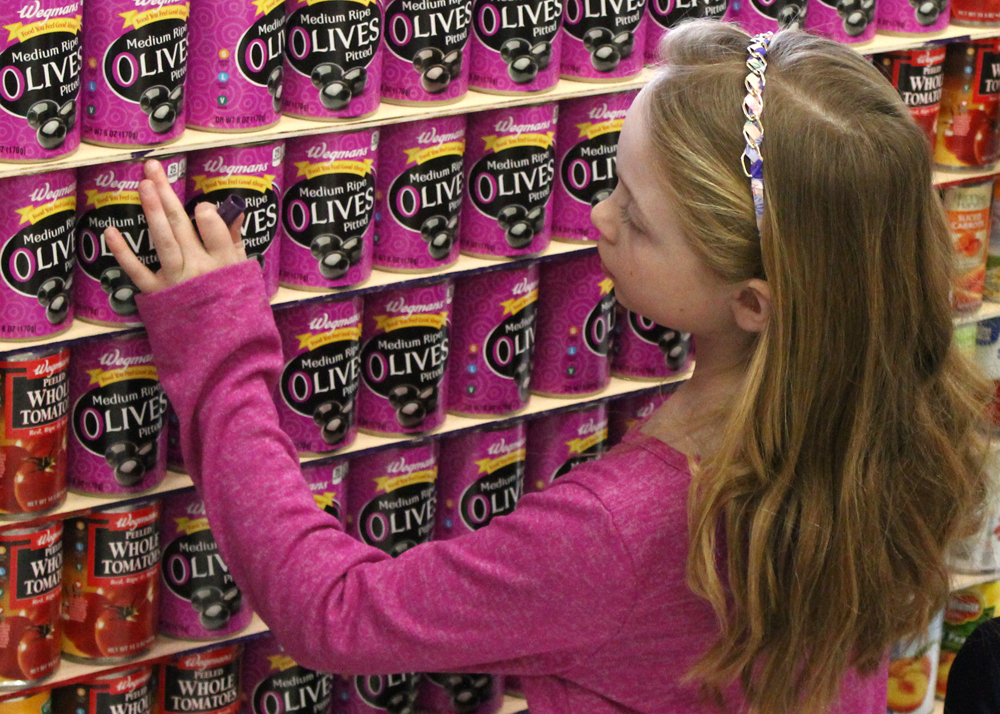 Grace Hasselberg adjusts pink-labeled cans and touches up the edges of the shelves.