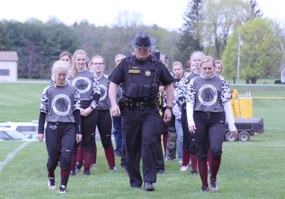 Byron-Bergen School Resource Officer and Marine Corps veteran Matthew Butler escorted by Byron-Bergen Varsity Softball players Lizzy and Becca. Photo by Gretchen Spittler