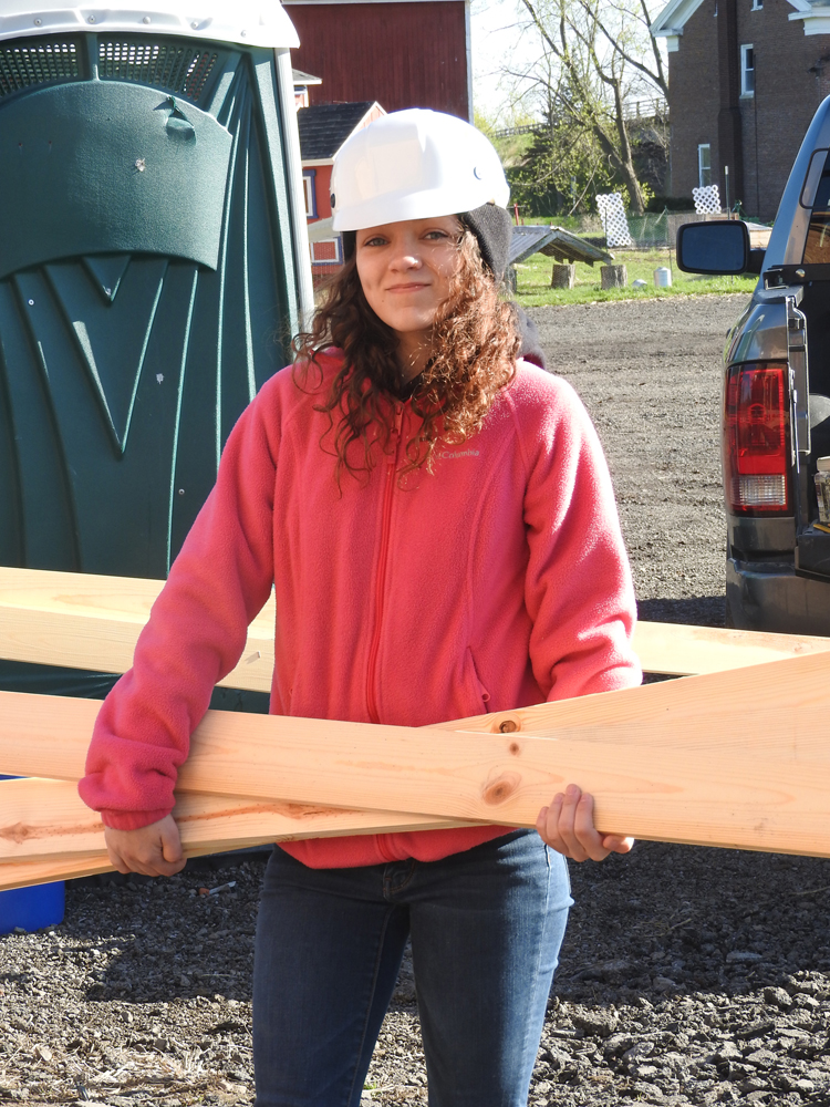 Makayla Famoly carrying lumber to the worksite.