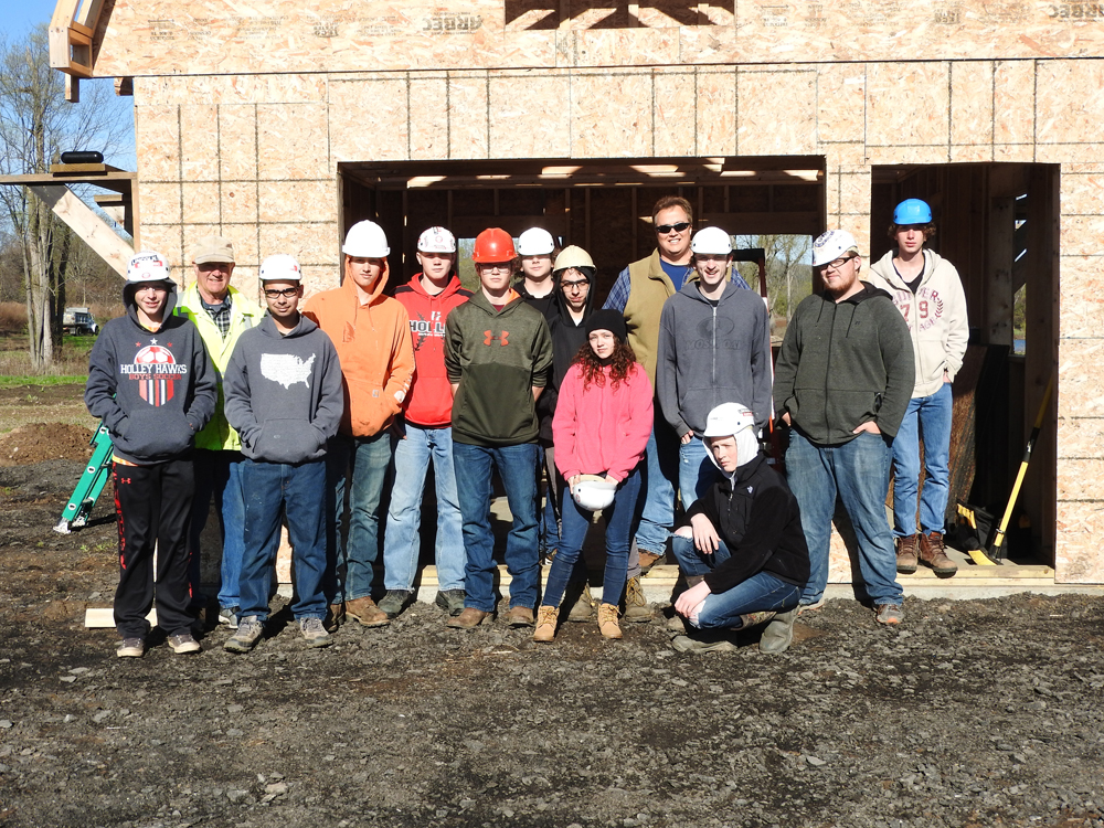 Holley's Geometry in Construction students and their instructors. Shown (l-r): Broek Ostrom, Tim Rogers (teacher), John Patt, Triston McFadden, Zach Dann, Jake Silpoch, Zach McAllister, David Farruggia, Makayla Famoly, Russ Albright (teacher), Evan Towsley, Storm Boyce (kneeling), Riley Weaver, and Alex Knopp.