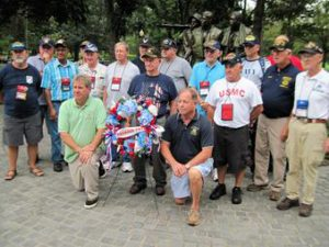 Assemblyman Steve Hawley, right of wreath, poses for a photo with Assemblyman Michael DenDekker, left of wreath, and veterans in front of the Vietnam War Memorial during last year's Patriot Trip to Washington D.C.