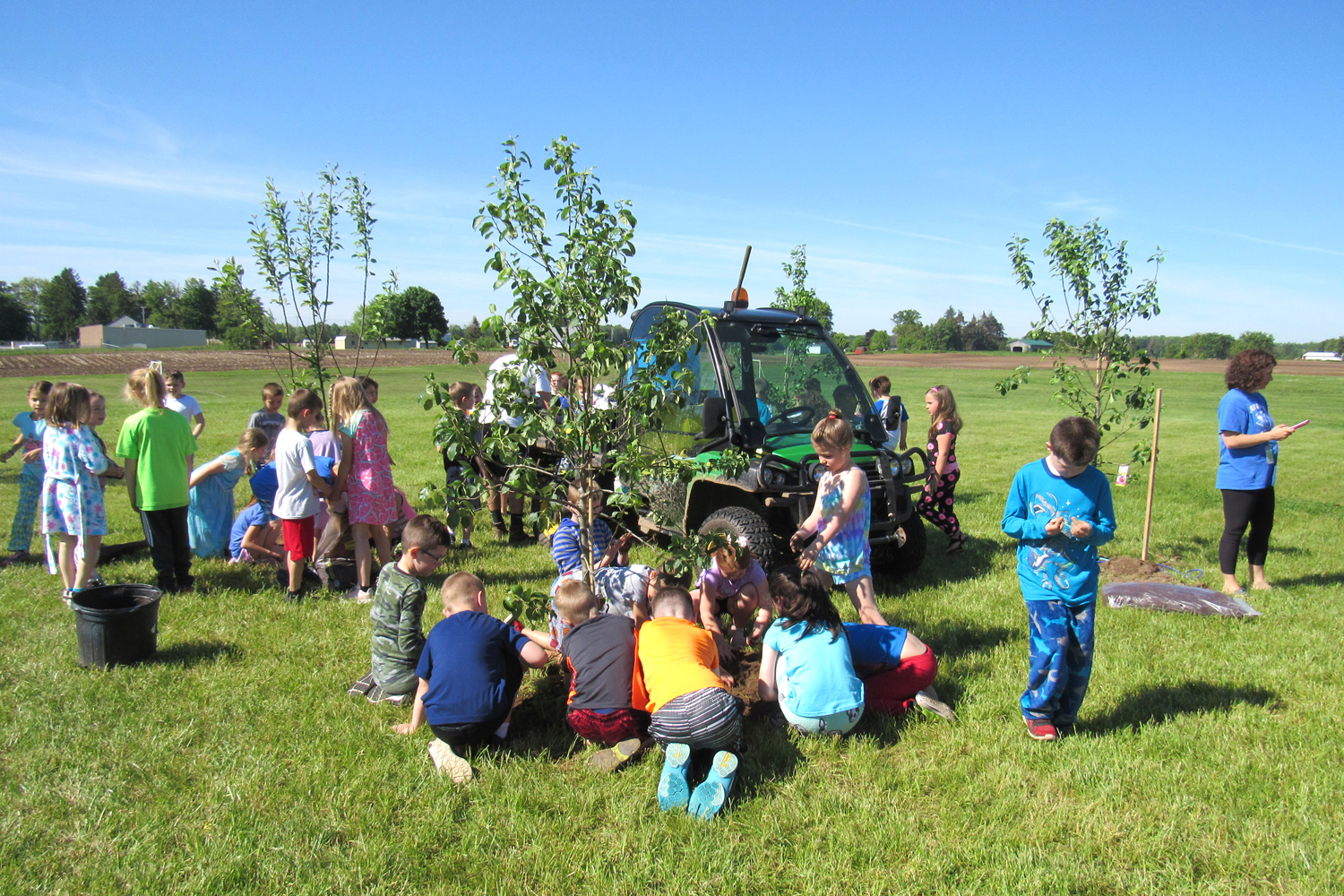 Kendall Elementary students work with school staff and administrators to plant a school orchard on Friday, June 7. Sara's Garden Center in Brockport donated the six fruit trees.