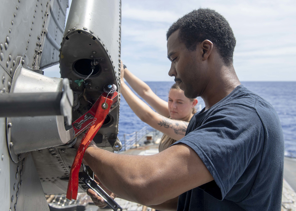 190614-N-WK982-1077 EAST CHINA SEA (June 14, 2019) Aviation Electronics Technician 2nd Class Shyhiem Rhodes, from Rochester, N.Y., right, and Aviation Machinist Mate Airman Kaitlynn Stout, from Gilbert, Az., raise the port stabilator on an MH-60R Sea Hawk aboard the Ticonderoga-class guided-missile cruiser USS Chancellorsville (CG 62). Chancellorsville is forward-deployed to the U.S. 7th Fleet area of operations in support of security and stability in the Indo-Pacific region. (U.S. Navy photo by Mass Communication Specialist 2nd Class John Harris/Released)