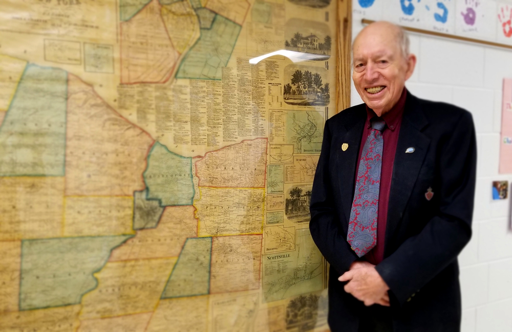 """Bill Andrews stands next to an 1858 Monroe County map, one of many maps on display in the second-floor hallway of Hill School. On February 15, he addressed the Hill School students about history. Ending his remarks, he said, """"There are many ways to learn about history, and many ways you can be involved in making history real for other people. The maps in your halls are only one small way, but they are a start. Make good use of them."""" Photo by Dianne Hickerson"""