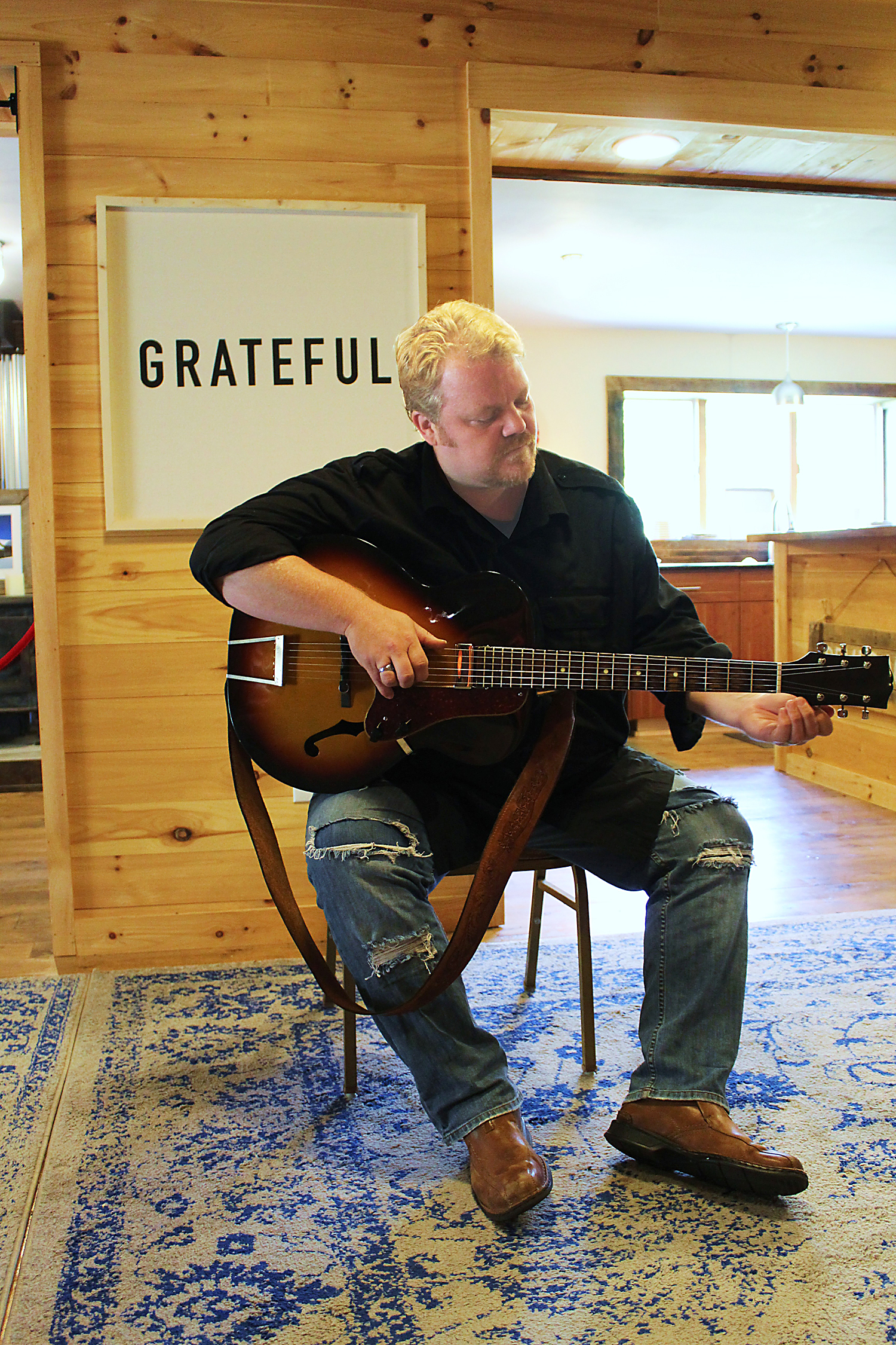 Chris Wilson strumming his guitar in front of the print that provides a daily focal reminder of his gratitude. Photo by Julia Mungenast
