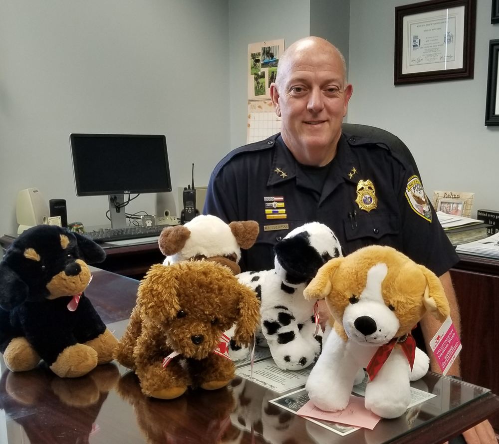 Brockport Police Chief Mark Cuzzupoli displays some of the nearly 40 donated stuffed animals the Police Department received. These toys will be carried in patrol cars to be given to children they may encounter in difficult situations. Photo by Dianne Hickerson