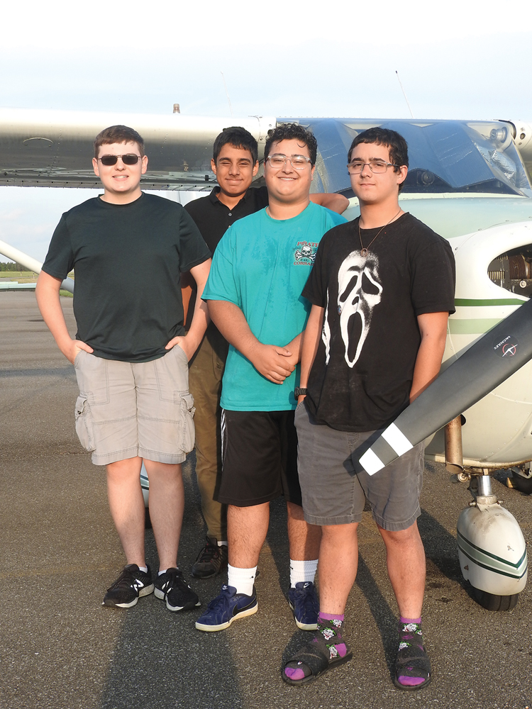 Tyler Mullen of Hilton, Dhruva Rana of Pittsford, Elio Dominguez-Montalbano and Elijah Brewer both from Greece by one of the planes at Ledgedale Airpark in Brockport.