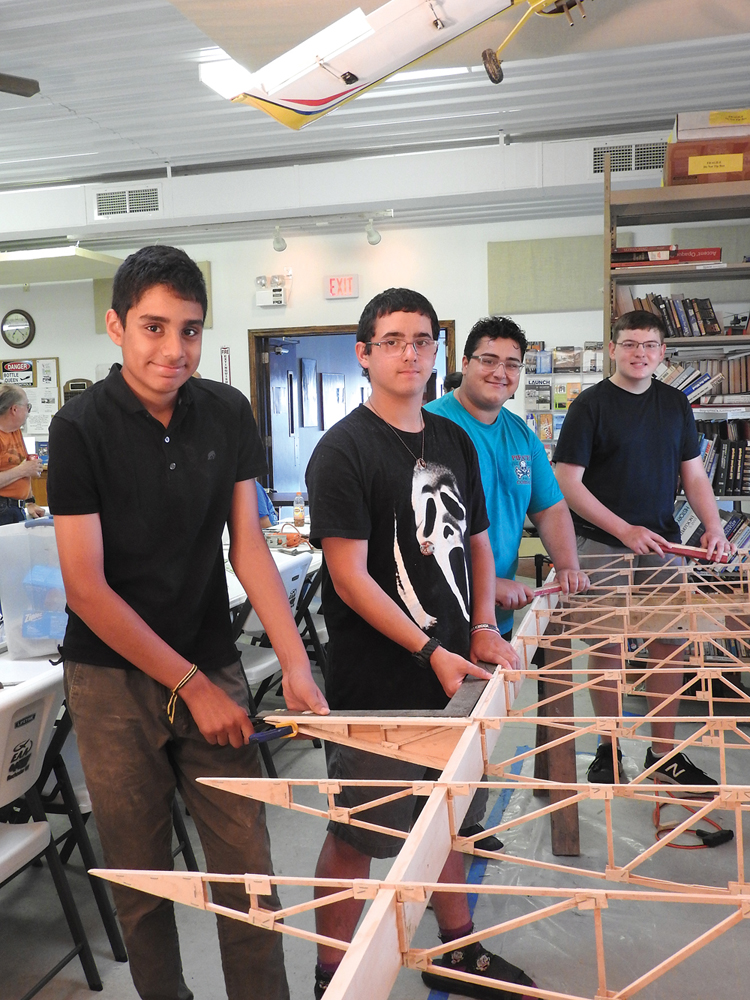 Dhruva Rana, Elija Brewer, Elio Dominguez-Montalbano and Tyler Mullen are working on the structure of the wing of a Corben Baby Ace. The ribs and spars of the wing are being smoothed on the leading edge of the wing.