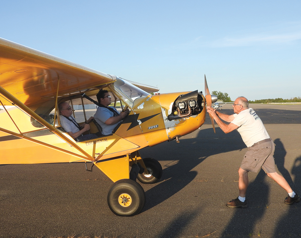 Vet Thomas and Elio Dominguez-Montalbano waiting for Earl Luce to get the propeller started.