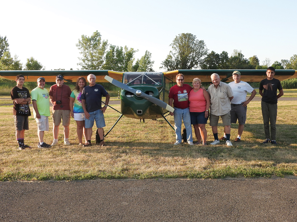 """The group standing with """"Buttercup"""" left to right: Elijah Brewer, Jason Brewer, Lauren Rosenthal, Clara Montalbano, Pete Bonneau, Bob Nelligan-Barrett, Gail Isaac, Bruce Willis, Earl Luce, and Dhruva Rana. Buttercup is a repluca of the original Wittman Buttercup in Oshkosh, Wisconsin and owned by Earl Luce."""