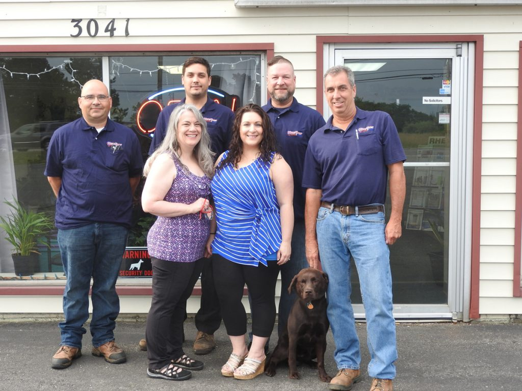 Huether Heating & Cooling is celebrating 50 years in business. Back row (l-r): Bob Michalowski, Dave Veator, Brian O'Connor and John Huether Jr. Front row (l-r): Barbara Clark, Holly Sibbald and furry family member Delilah Huether.