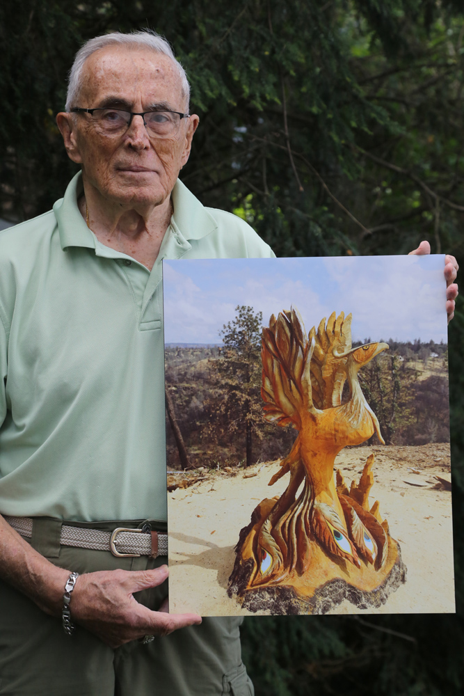 Walt Horylev holds a photo he took of The Phoenix, a bird representing a rebirth, rising from the ashes of a fire. The image of hope was created by Jesse Groeschen, a female chainsaw artist from Trinidad, California. It's a sculpture fashioned out of a six foot high tree trunk that sat alongside the Skyway, the main road out of Paradise, California. A tree in the background to the right of the sculpture was edited out to give better clarity to the right side of the bird. Photo by Jan Clements