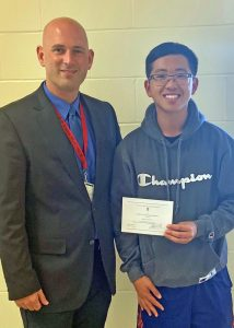 Dr. Jeffrey Green, Hilton High School principal, presents senior Brian Phung with a Letter of Commendation from the National Merit Scholarship Corporation.