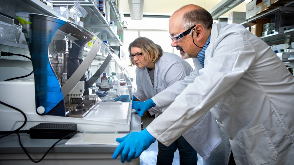 Sarah Poole and Joel Tabb of Ionica Sciences watch as samples are distributed onto a proprietary Lyme disease assay plate using an automated liquid handling system. Photo by Lindsay France/Cornell University.