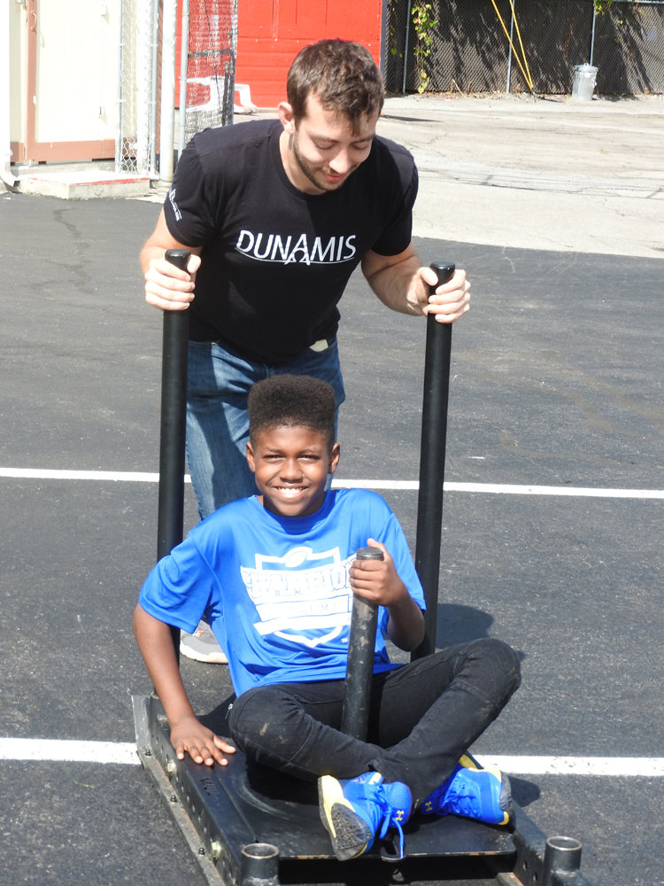Will Barker demonstrates sled pushing with De'Anthony Smith-Armstrong (sitting) at the Dunamis fitness challenge and yard sports zone.