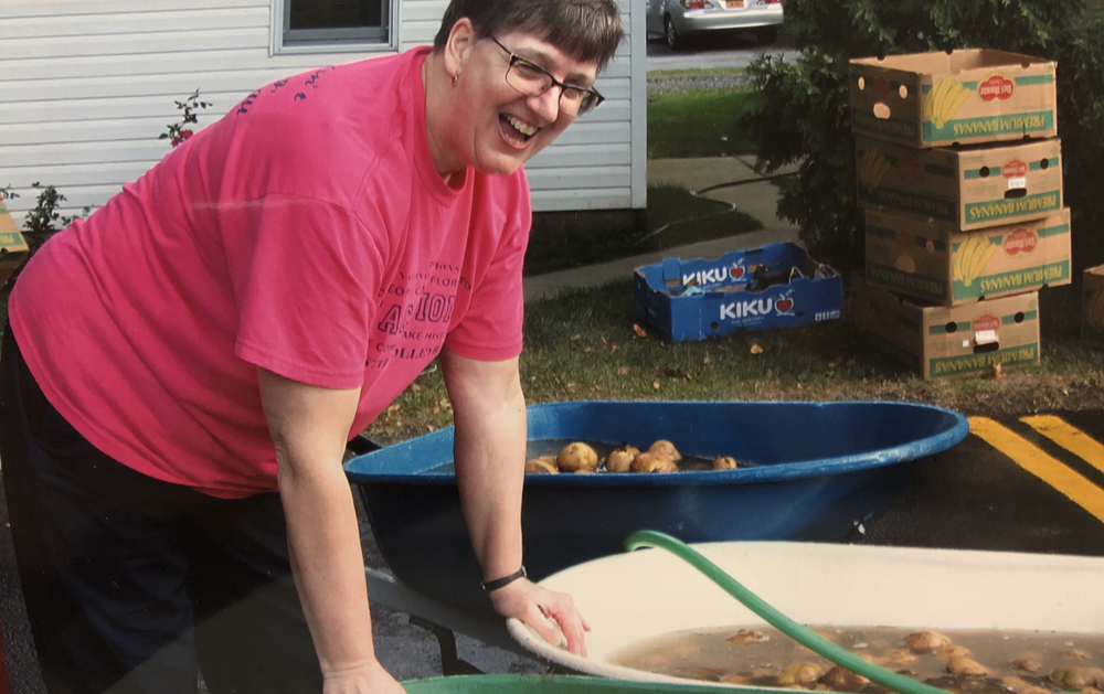 "Byron-Bergen Girls Varsity Volleyball Coach Cindy D'Errico takes part in the annual ""potato scrub."""
