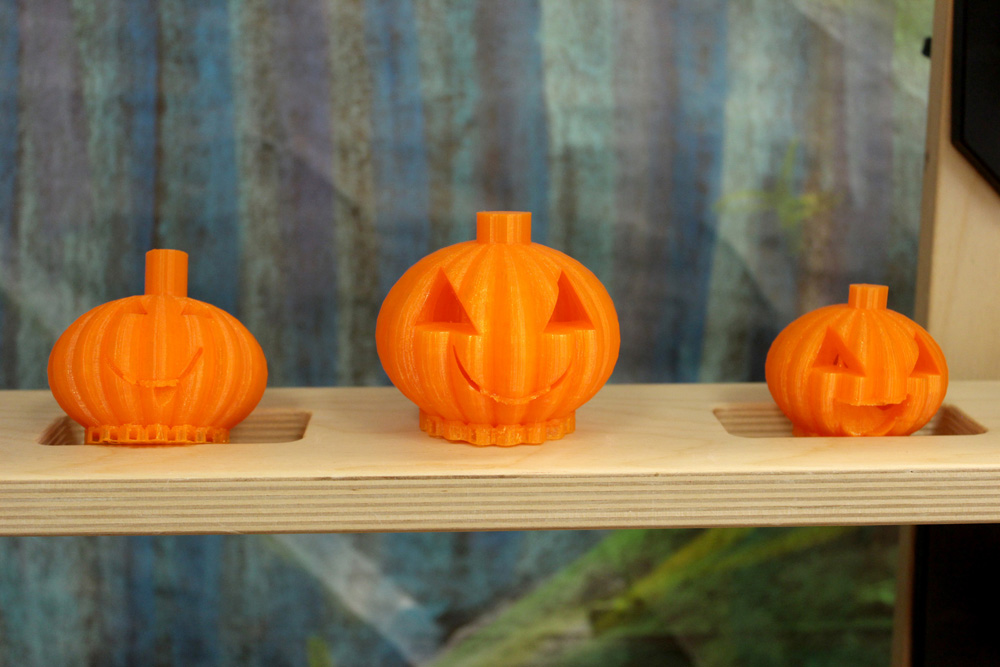 A closer view of some of the 3-D printed pumpkins on display. Pumpkins printed in a variety of colors – orange, blue, and purple.