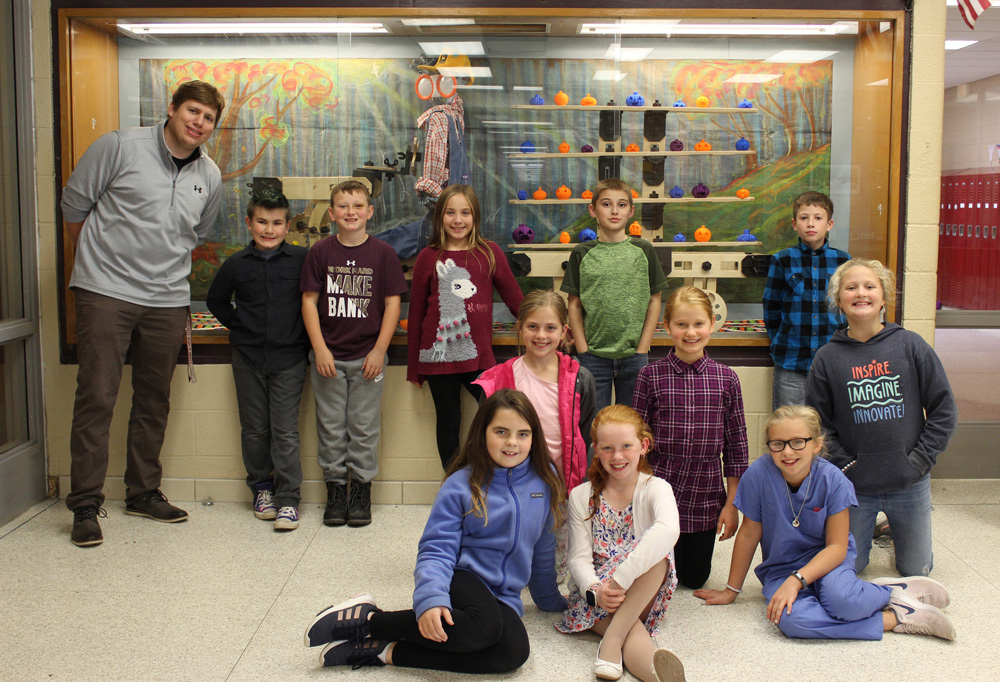 Craig Schroth with fifth grade students in front of 3-D printed pumpkin display case.