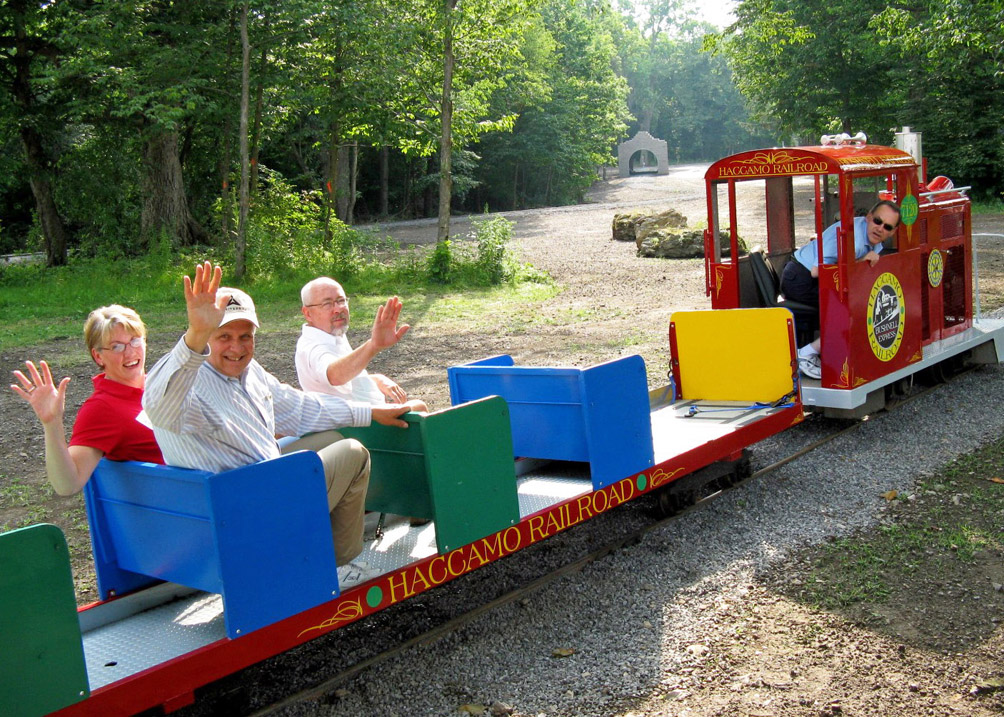 Former presidents Pam and Fred Kimmel and Art Appleby ride the Haccamo Express with former District 7120 governor Bill Gormont of Greece Rotary as engineer. The miniature train originally purchased, rehabbed, and installed at the old Camp Haccamo is now located at Rochester Rotary's Camp Sunshine in Rush.