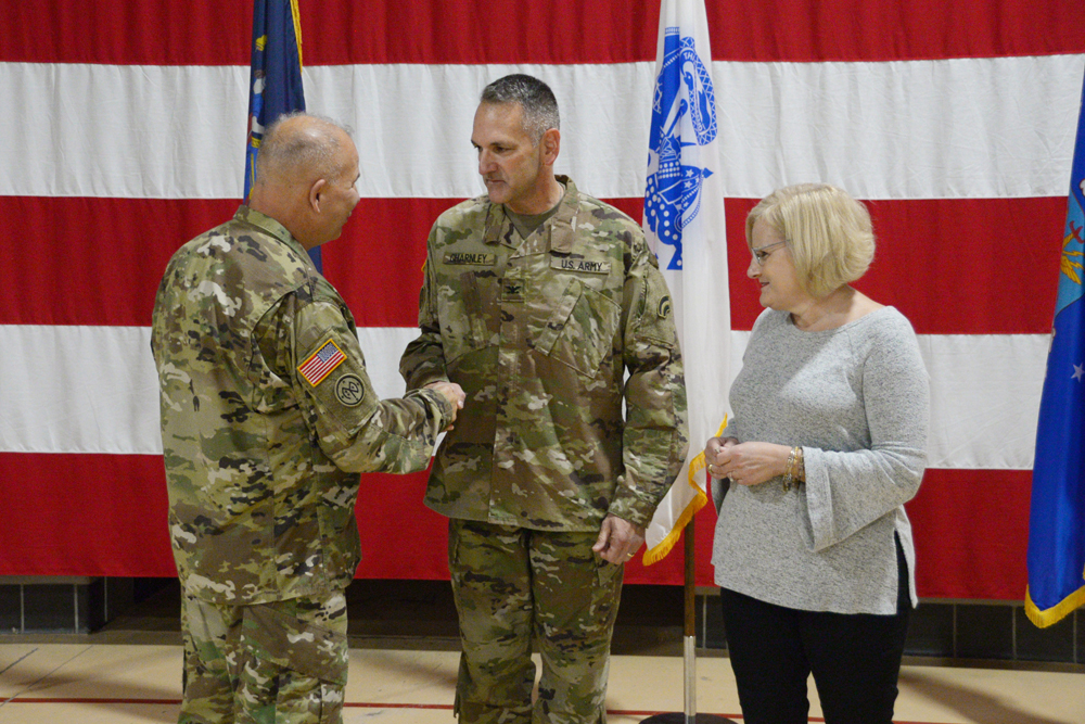 Col. Michael Charnley (center), a Churchville resident and commander of the 42nd Combat Aviation Brigade, is congratulated by Maj. Gen. Raymond Shields, the Adjutant General of New York, as his wife Karen looks on, following his promotion to Colonel during a ceremony at the Division of Military and Naval Affairs, on October 2. (U.S. Army National Guard photo by Ryan Campbell)