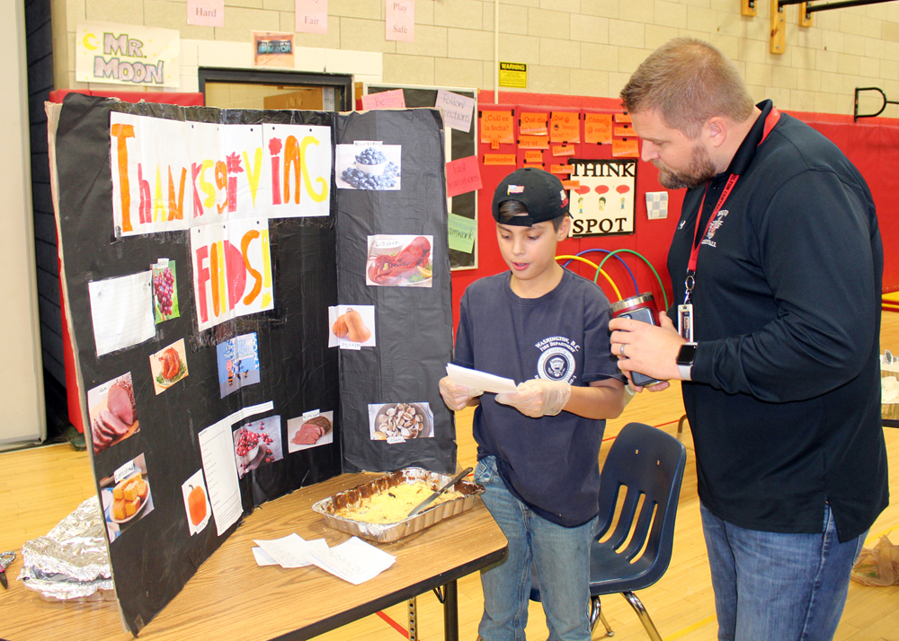 Jackson Harvill, an intermediate student at Quest Elementary School, talks to Principal Derek Warren about Thanksgiving foods enjoyed by the Pilgrims and Native Americans.